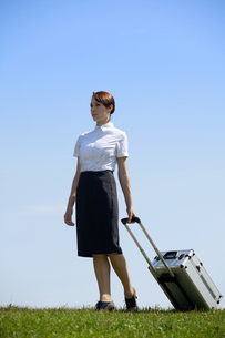 Businesswoman in contemplation holding luggage in parkの写真素材 [FYI03655869]