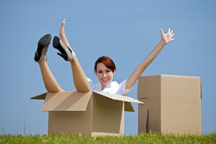 Portrait of cheerful young woman sitting in cardboard box at park with arms outstretchedの写真素材 [FYI03655886]