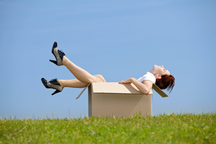 Young woman sitting in cardboard box at parkの写真素材 [FYI03655890]