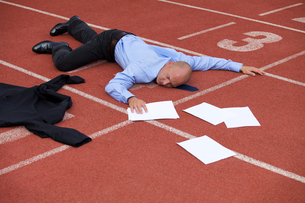 View of a businessman lying on a race trackの写真素材 [FYI03655915]