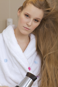 Portrait of a woman using a hairdryerの写真素材 [FYI03655989]