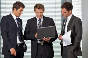 Businessmen looking at laptop in officeの写真素材 [FYI03656006]