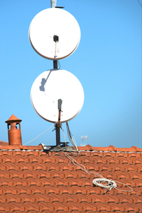 Satellite dishes on a tiled roofの写真素材 [FYI03656071]