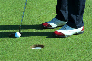 Close up of person putting golf ball on golf courseの写真素材 [FYI03656079]