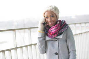 Happy woman in winter wear using cell phone outdoorsの写真素材 [FYI03656101]