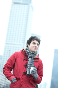 Thoughtful man in warm clothing holding disposable cup outdoorsの写真素材 [FYI03656117]