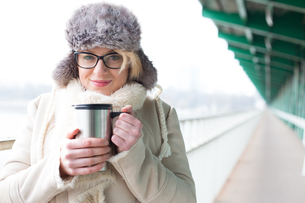 Portrait of smiling woman in warm clothing holding insulated drink containerの写真素材 [FYI03656121]