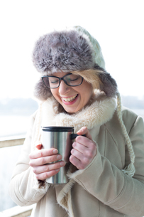 Cheerful woman in warm clothing holding insulated drink containerの写真素材 [FYI03656122]