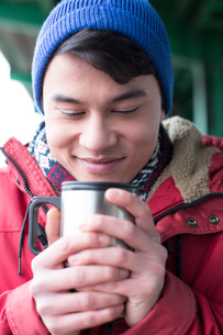 Smiling man looking at coffee in insulated drink container during winterの写真素材 [FYI03656127]