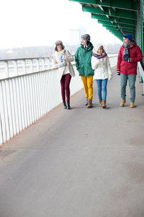 Multiethnic friends walking on footpath during winterの写真素材 [FYI03656130]