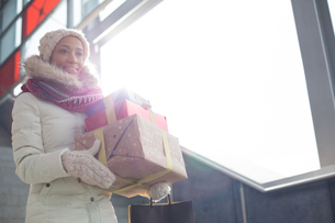 Smiling woman in warm clothing carrying stacked gifts by windowの写真素材 [FYI03656137]