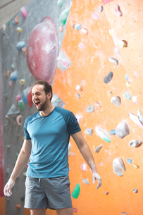 Dedicated man shouting by climbing wall in crossfit gymの写真素材 [FYI03656150]