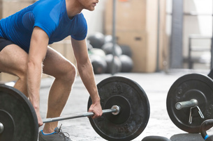 Low section of dedicated man lifting barbell in crossfit gymの写真素材 [FYI03656168]