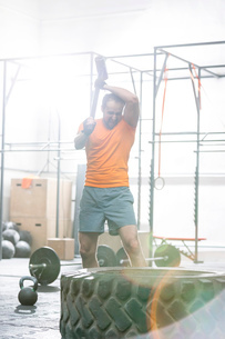 Determined man hitting tire with sledgehammer in crossfit gymの写真素材 [FYI03656179]