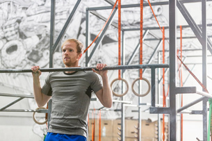 Confident man doing chin-ups in crossfit gymの写真素材 [FYI03656195]