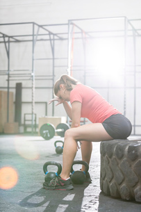 Tired woman sitting on tire in crossfit gymの写真素材 [FYI03656206]