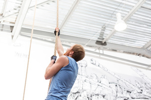Side view of dedicated man climbing rope in crossfit gymの写真素材 [FYI03656219]