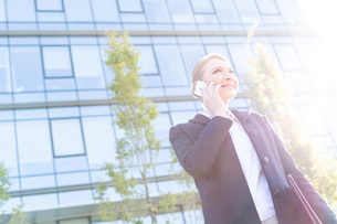 Low angle view of smiling businesswoman using cell phone on sunny dayの写真素材 [FYI03656243]
