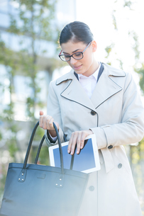 Businesswoman putting digital tablet in bag outdoorsの写真素材 [FYI03656244]