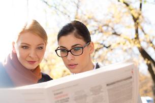 Businesswomen reading newspaper at parkの写真素材 [FYI03656255]