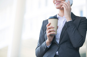 Midsection of businesswoman using cell phone while holding disposable cup outdoorsの写真素材 [FYI03656269]