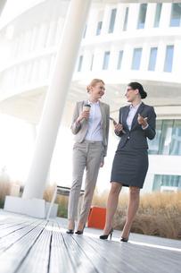 Full-length of businesswomen conversing outside office buildingの写真素材 [FYI03656273]