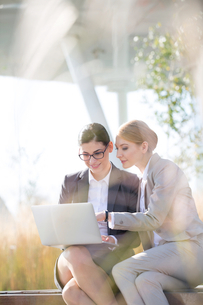 Happy businesswomen using laptop together on sunny dayの写真素材 [FYI03656280]