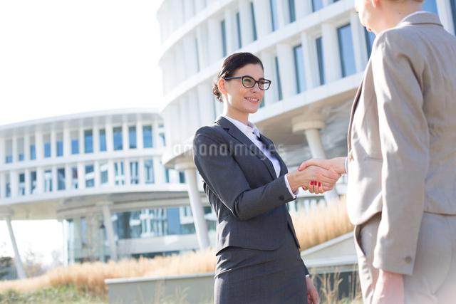 Happy businesswomen shaking hands outside office buildingの写真素材 [FYI03656281]