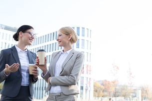 Happy businesswomen conversing while holding disposable cups outside office buildingの写真素材 [FYI03656282]