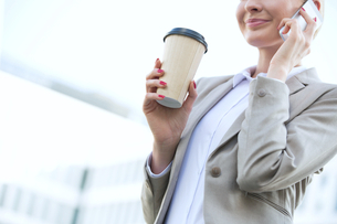 Midsection of businesswoman using cell phone while holding disposable cup outdoorsの写真素材 [FYI03656285]