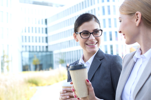Happy businesswomen conversing while holding disposable cups outdoorsの写真素材 [FYI03656287]