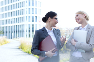 Cheerful businesswomen conversing while holding folder and laptop outside office buildingの写真素材 [FYI03656293]