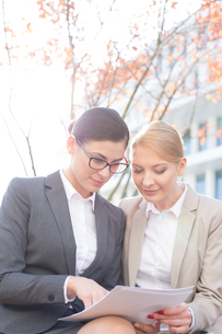 Businesswomen reading papers while sitting outdoorsの写真素材 [FYI03656298]