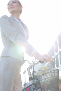 Low angle view of businesswoman standing with bicycle on sunny dayの写真素材 [FYI03656309]
