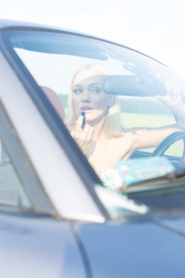 Woman applying lipstick in convertible on sunny dayの写真素材 [FYI03656335]