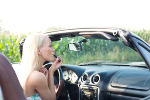 Rear view of woman applying lipstick in convertibleの写真素材 [FYI03656348]