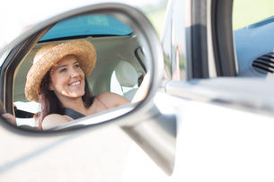 Reflection of happy woman in rearview mirror of carの写真素材 [FYI03656364]