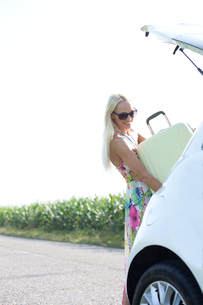 Happy woman loading suitcase in car trunk against clear skyの写真素材 [FYI03656371]