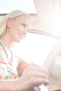 Low angle view of smiling woman driving carの写真素材 [FYI03656377]