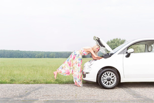 Full-length side view of woman examining broken down car on country roadの写真素材 [FYI03656382]