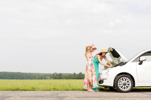 Friends examining broken down car on country road against clear skyの写真素材 [FYI03656383]