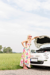 Full-length of tensed woman standing by broken down car on country roadの写真素材 [FYI03656384]