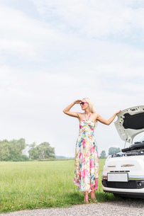 Woman shielding eyes while standing by broken down car on country roadの写真素材 [FYI03656385]
