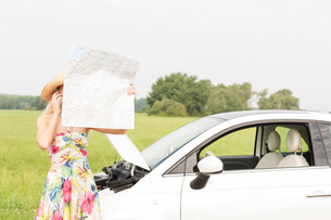 Woman using cell phone while reading map by broken down car at countrysideの写真素材 [FYI03656389]
