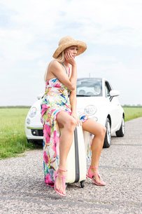 Full length of irritated woman sitting on luggage by broken down carの写真素材 [FYI03656392]