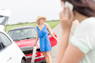 Angry woman standing by damaged cars with female using cell phone in foregroundの写真素材 [FYI03656394]