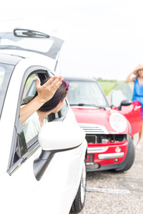 Angry woman gesturing while talking to female crashing car on roadの写真素材 [FYI03656395]