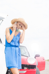 Tensed young woman using cell phone by broken down carsの写真素材 [FYI03656397]