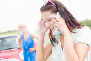 Worried woman using mobile phone while friend standing by broken down car on sunny dayの写真素材 [FYI03656398]