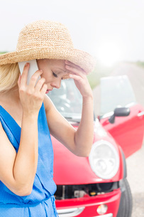 Tensed young woman using cell phone by broken down carの写真素材 [FYI03656399]